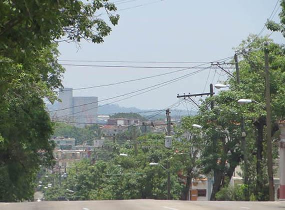 Tendido eléctrico y árboles sin podar en la Calzada de Porvenir, Lawton